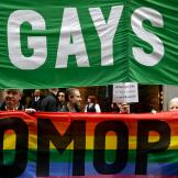 FILE- In this March 17, 2015 file photo, protesters hold signs protesting the exclusion of LGBT groups during the St. Patrick's Day Parade in New York. A year after a limited easing of the parade's prohibition on gay groups, organizers now have opened the lineup more broadly to include activists who protested the ban for years. (AP Photo/Seth Wenig, File)